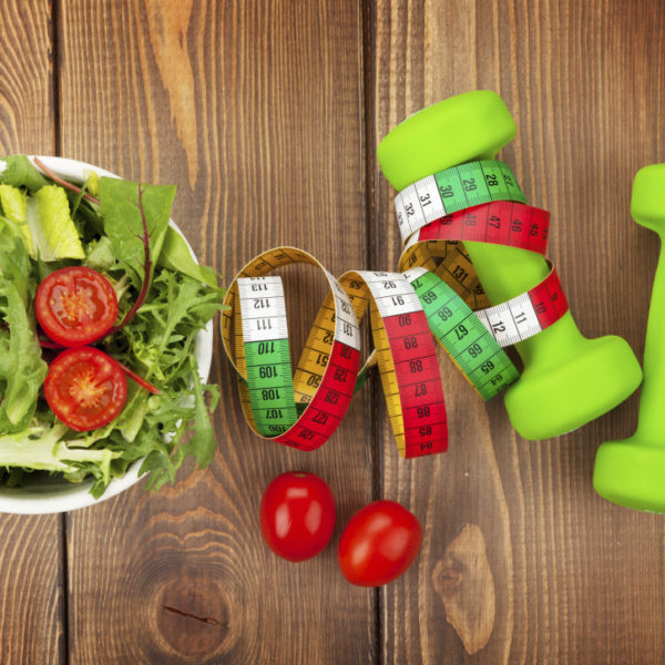 Dumbells, tape measure and healthy food over wooden table. Fitness and health