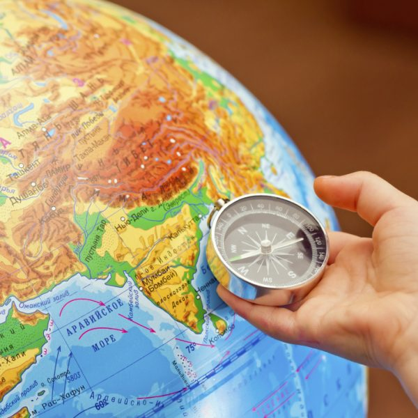 Compass in a child's hand against the globe.
